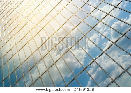 Dirty Windows Of A Newly Built Office Building Reflecting The Blue Sky With Clouds. Clouds Reflected