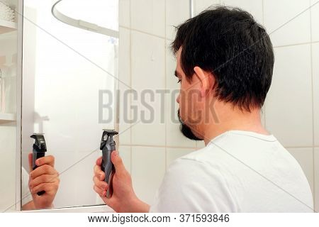 Adult Man With Disheveled Hair Standing In Front Of Mirror And Looking At Hair Trimmer (clipper). Mi