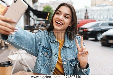 Image of smiling woman taking selfie on cellphone and gesturing peace sign while sitting at street cafe outdoors