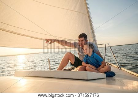 Happy traveler father and son enjoying sunset from deck of sailing boat moving in sea at evening time. Bonding Travel, Summer, Holidays, Journey, Trip, Lifestyle, Yachting concept.