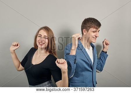 Arms Up Celebrating Success Fists In Exultation. Young Attractive Couple Boyfriend Girlfriend Two Pe