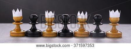 White Pawns With A Paper Crown On Their Heads And Black Pawns Without A Crown. Racism, Black Lives M