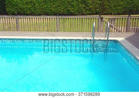 Modern Swimming Pool With Pool Cover For Protection Dirt Rolled Up And Pool Ladder In Garden.