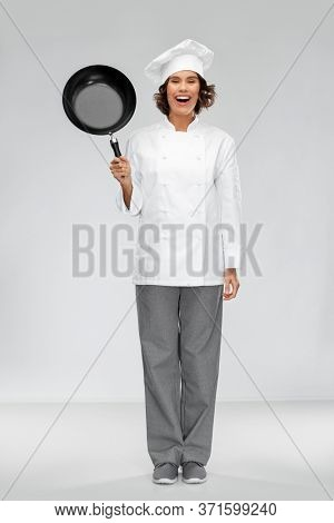 cooking, culinary and people concept - happy smiling female chef in toque with frying pan over grey background