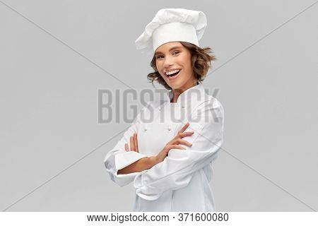cooking, culinary and people concept - happy smiling female chef in toque with crossed arms over grey background