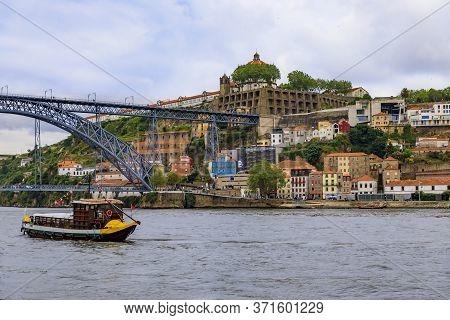 View Across The Douro River And Dom Luis I Bridge In Vila Nova De Gaia And Tourist Boats That Were U