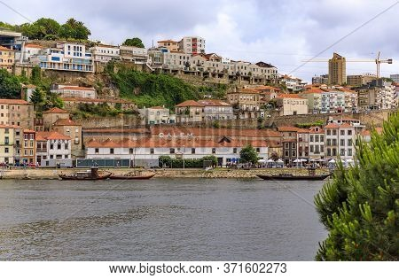 Porto, Portugal - May 30, 2018: View Across The Douro Onto Rabelo Boats With Barrels Of Port Docked