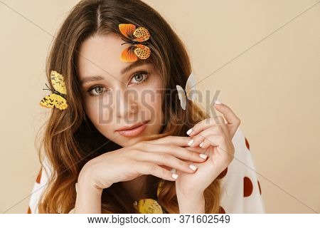 Photo of beautiful pleased woman with fake butterflies posing and looking at camera isolated over beige wall