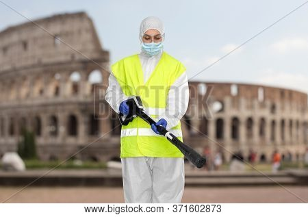 disinfection and pandemic concept - sanitation worker in protective gear or hazmat suit, medical mask, gloves and goggles with pressure washer or sanitizer over coliseum in rome, italy on background