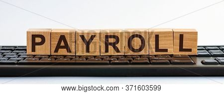 Payroll Word Made With Building Blocks. A Row Of Wooden Cubes With A Word Written In Black Font Is L