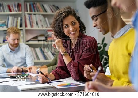 Multiethnic business people discussing together their strategy. Happy businesswoman showing marketing strategy african businessman. Creative business team talking and smiling during brainstorming.