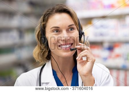 Mid adult woman pharmacist talking to client in a pharmaceutical call center. Medical worker taking home delivery order of medicine by phone. Doctor consulting and help in service customer support.