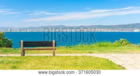 Bench On The Sunny Beach Shore. Beautiful View From  Paved Footpath On The Seaside. City And Mountai