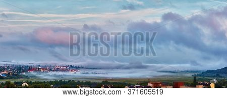 Morning Mist Is Like Huge Waves, That Cover A Sleeping City In A Valley. Uzhhorod, Ukraine