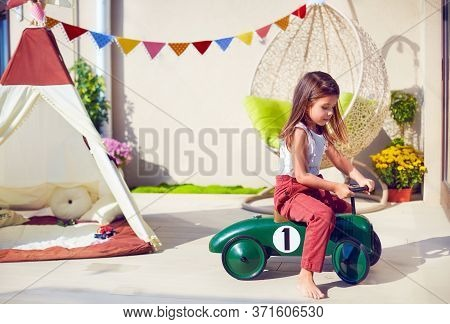 Cute Young Girl, Child Riding A Toy Car, Playing On Summer Patio