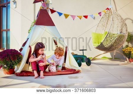 Cheerful Kids Are Playing Toys On Summer Patio At Sunny Day