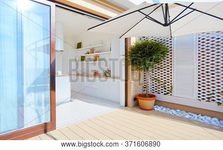 Rooftop Deck Patio Area With Sliding Doors And Open Space Kitchen At Summer Day
