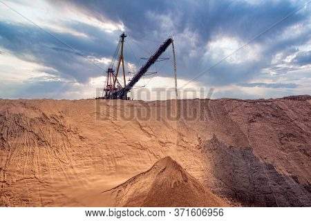 Industrial Background. Salt Mining Site Under A Sky With Dramatic Clouds. Large Excavator Machine An