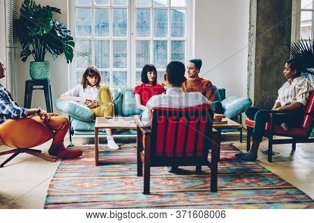 Trendy Female Communicating With Friends During Gathering