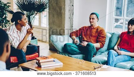 Pleasant Black Woman Talking To Man Pointing With Hand In Meeting