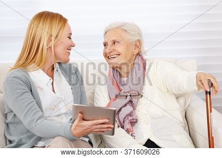 Smiling adult woman showing a tablet computer to a senior citizen