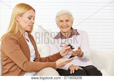 Woman measures the blood sugar level with a measuring device in a senior citizen with diabetes mellitus