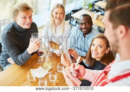 Young people as guests order food from a waiter in the restaurant or bar