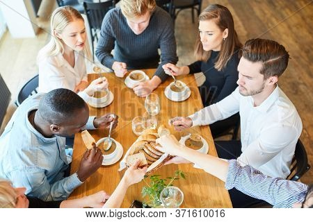 Group of young people eating soup as an appetizer in the restaurant