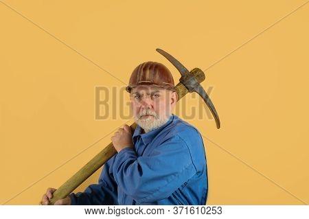 Builder Man Holds Pickaxe. Craftsman Working With Pickaxe. Man Holding Pick-axe. Male Miner Worker I
