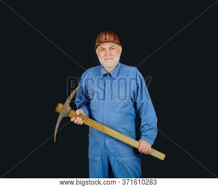 Smiling Workman With Pickaxe. Male Bricklayer In Hard Hat With Pickaxe. Construction Worker Holds Pi
