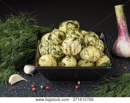 Young Boiled Potatoes With Dill And Garlic. Black Background.