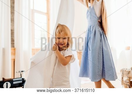 Young Mom Or Babysitter Playing With Little Child At Home
