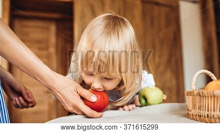Little Girl Bites An Apple That Is Held By A Mom Or A Babysitter Sitting At The Table