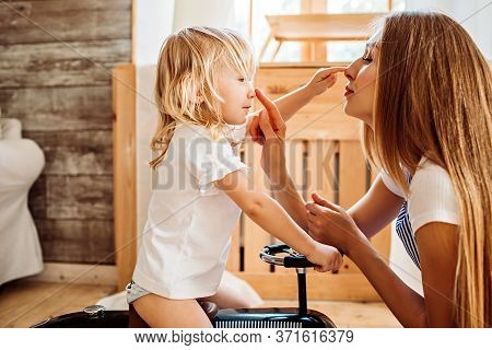 Young Mother Teaches Her Little Daughter Simple Words, Showing Parts Of Her Face