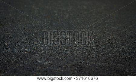 The Surface Of The Black Asphalt Is A Soft Focus. Dark Tar Asphalt Background Texture At An Angle Of