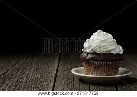 A Chocolate Cupcake In A Typical Fluted Cupcake Liner, Topped With Whipped Cream And Decorated With