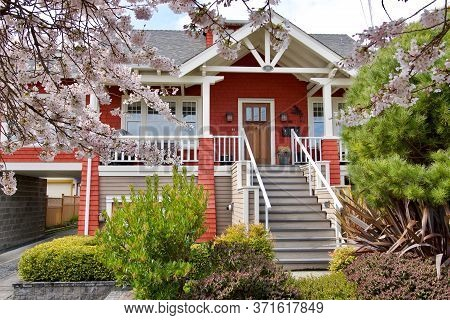 Victoria, British Columbia, Canada, March 24, 2020: Pretty Orange House Framed By Trees And Cherry B