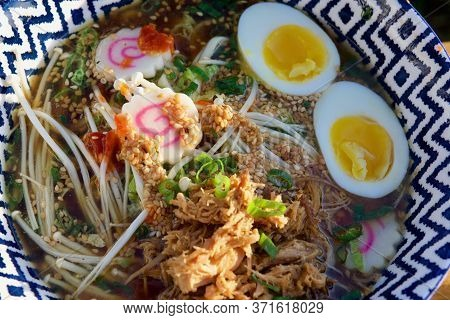 Colourful Bowl Of Mushroom And Pulled Pork Ramen With Soft Boiled Egg And Sesame Seeds Seen Up Close