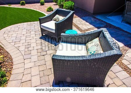 Outdoor Wicker Arm Chairs On Pavers Patio