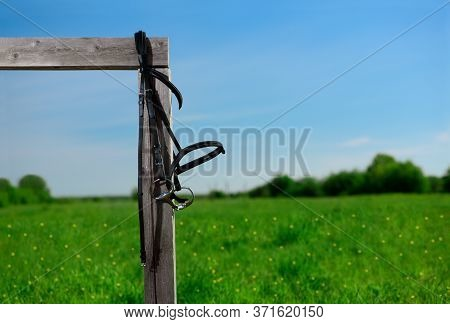 The Black Leather Snaffle Bridle Is Hanging On The Wooden Hitching Post On Against The Landscape.