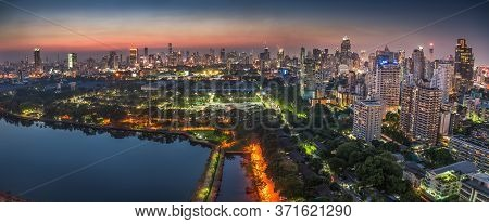 Wide Panoramic View Of Bangkok, Thailand. Cityscape With Public Park And Skyscrapers At Twilight.