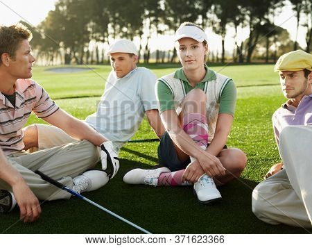 Four young golfers sitting on court