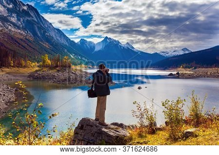 Tourist with a photo bag photographs the mountain lake of Medicine. Canada, Alberta, Jasper. Great autumn day. The concept of active, environmental and photo tourism