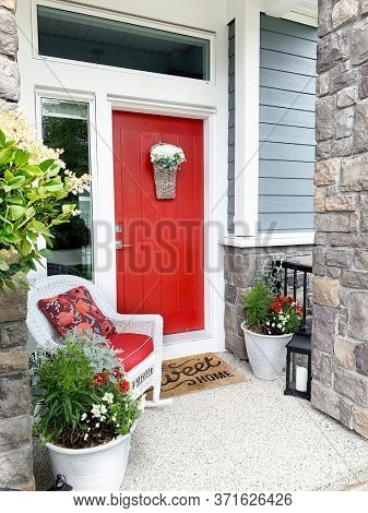 Front door painted orange and a wicker chair on the porch. Colorful entrance.