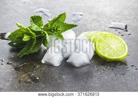 Green mint leaves, ice cubes and sliced lime on black table.