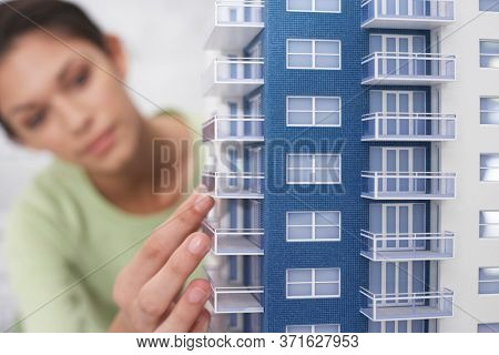 Mid adult woman inspecting architectural model close-up