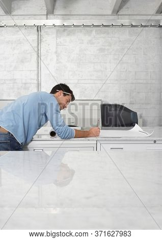 Mid adult man drawing on sheet of paper side view