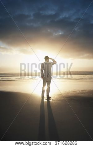 Rear view of businessman standing on beach looking to the horizon at sunset