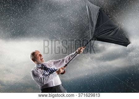 Businessman struggling to keep hold of inside-out umbrella in storm