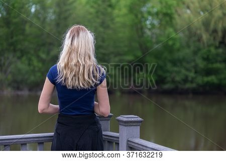 Woman Looking Away At The Lake And The Trees